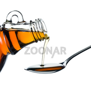 maple syrup pouring on spoon
