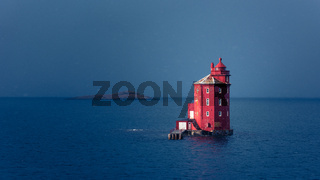 Famous red lighthouse  Kjeungskaer in the middle of the ocean near the Norwegian coast in snow storm
