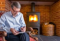 Senior man checking a document with wood fire in background