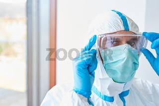 Arzt in Klinik mit Schutzkleidung und Schutzbrille