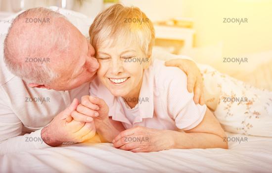 Alter Mann küsst Frau im Bett