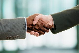 Interracial handshake on business background