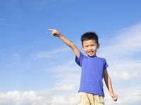 happy little boy pointing direction with blue sky background