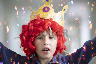 Child in a red wig and a crown. Clown boy in shiny candy
