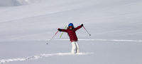 Happy girl on off-piste slope with new fallen snow at nice sun day