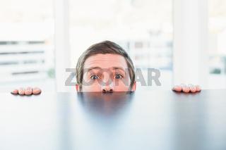 Nervous businessman peeking over desk