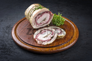 Traditional Italian panchetta arrotolata pork meat sliced and as piece with herbs offered as close-up on a rustic wooden board with copy space
