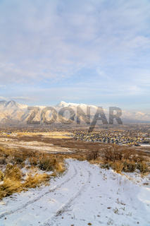 Snowy dirt road on hill with views of neighborhood houses and Mount Timpanogos