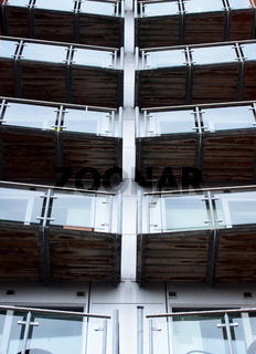 vertical perspective view of angled modern glass apartment balconies on a blue steel building