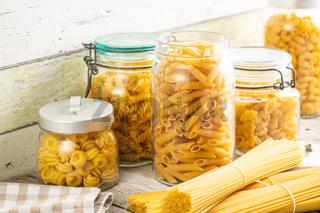 Various types of raw italian pasta in jars.