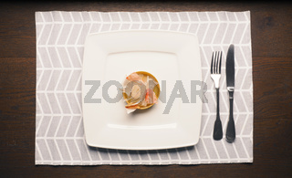 plastic garbage on a plate with cutlery on a wooden table