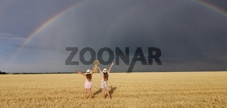 In a wheat field after the rain, two girls run. Colorful real rainbow over the horizon. europe Ukraine. Summer crop fields, ripening wheat field.