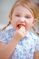 Kleines Kind beißt in Erdbeere