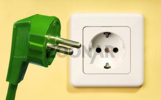 Steckdose und grüner Stecker
