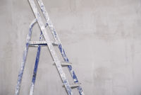 Single aluminum folding metal step ladder leaning against white plaster wall background