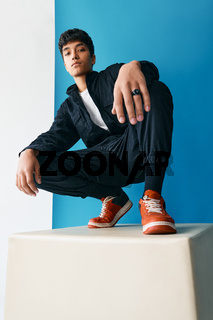 Confident young trendy mixed race man posing in studio sitting on big cube