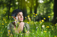 black haired woman lying in grassland
