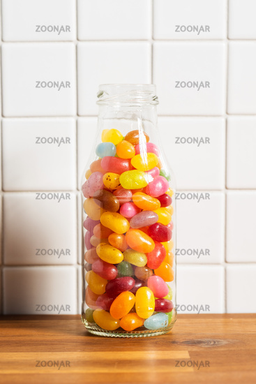 Fruity jellybeans. Tasty colorful jelly beans in glass bottle