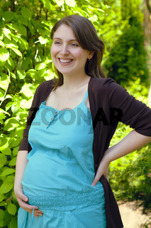 Happy pregnant woman in green park