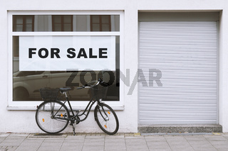 for sale sign in store window with bicycle parked outside - shop vacancy