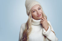 Beautiful woman in white knitted sweater and hat