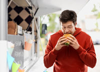 hungry young man eating hamburger at food truck