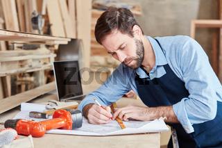 Handwerker in Werkstatt zeichnet Plan