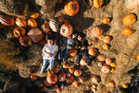 Young girls lie on haystacks among pumpkins. View from above