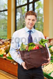 Mann kauft frisches Gemüse im Biomarkt