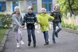 Belarus, the city of Gomel, May 10, 2019. Open day in kindergarten.Happy preschoolers on the street. Children holding hands jumping. A group of six year old friends.