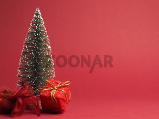 Red Christmas gift box with golden bow and decoration on a red paper background