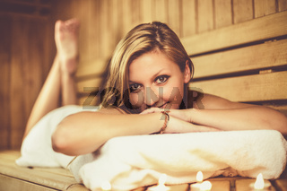 Lady relaxing in traditional wooden Finnish sauna.