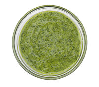 Pesto sauce in a glass bowl on white background