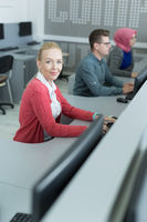 Beautiful blonde woman working in her office. Cooperating office space. Sharing office with colleagues.