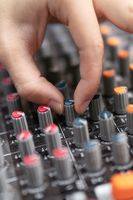 Close-up of a mixing console, hand equalizing audio channels. Professional recording studio. Working in recording studio.
