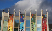 the brightly coloured facade of the new west yorkshire playhouse theatre building against a bright cloudy blue sk