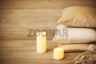 Comfortable cushions and white burning candles in cozy living room