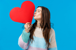 Romance, love and tenderness concept. Feminine cheerful and cute brunette woman showing her feelings, kissing big red heart card with closed eyes, express sympathy and care, blue background