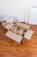 Moving boxes with packing material for fragile items on the floor. Concept of moving in or out.