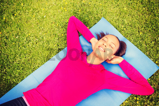 smiling woman doing exercises on mat outdoors