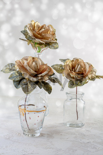 Golden roses in glass vases.