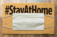 Welcome Mat With Medical Face Mask and #Stay At Home Text Amidst The Coronavirus Pandemic