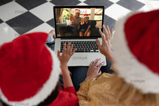 Rear view of woman and daughter in santa hats waving while having a videocall with man and son in sa