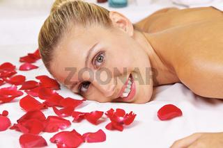 Frau liegt im Spa neben Rosenblättern