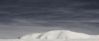 Snowy ski slope at high winter mountains and sunlit cloudy sky