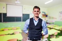 Portrait of a male teacher, empty classroom on background