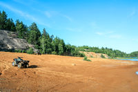 Quad ATV stands on sandy terrain at a beautiful lake.