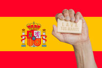 Male hand holding bar of soap with words: Lava tus manos, in Spanish