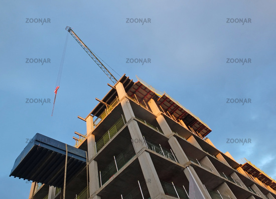 a vertical corner view of a crane on a construction site with a concrete framework against a blue sunlit sky