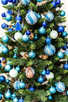 Green Christmas Tree With Beautiful White and Blue Decorations.